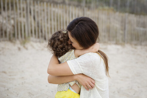 Happy mother hugging little daughter on the beach - LITF00455
