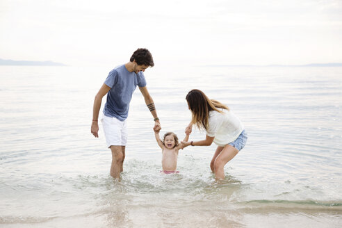 Parents playing in the sea with their little girl - LITF00458