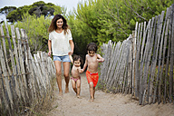 Happy mother and two children walking hand in hand on beach path - LITF00464
