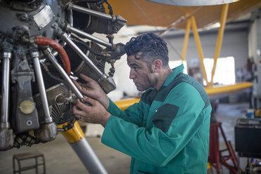Mechanic in hangar repairing light aircraft - ZEF12137