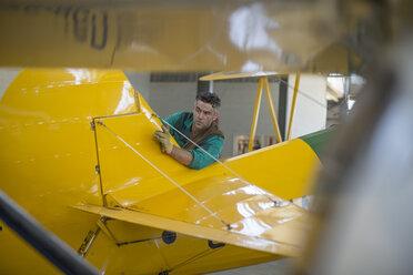 Mechanic in hangar repairing light aircraft - ZEF12155