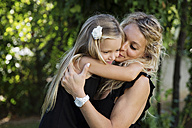 Mother hugging and kissing her little daughter in the garden - LITF00467
