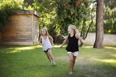 Two little sisters running in the garden - LITF00470