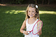 Portrait of smiling blond girl with badminton racket - LITF00476