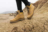 Spain, Navarra, Bardenas Reales, hiking shoes of young woman in nature park, close-up - KKAF00250
