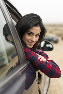Young woman leaning out of car window - KKAF00262