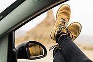 Spain, Navarra, Bardenas Reales,  legs of young woman leaning out of car window - KKAF00268