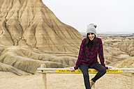 Spain, Navarra, Bardenas Reales, smiling young woman sitting on barrier in front of nature park - KKAF00271
