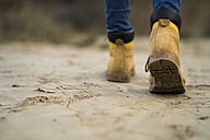 Spain, Navarra, Bardenas Reales, hiking shoes of young woman walking in nature park, close-up - KKAF00283