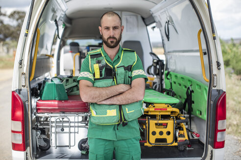 Paramedic standing with arms crossed in front of ambulance - ZEF12172