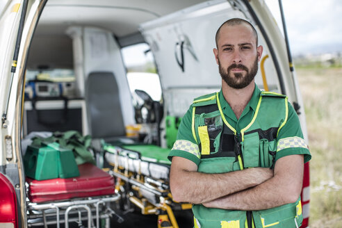 Paramedic standing with arms crossed in front of ambulance - ZEF12175
