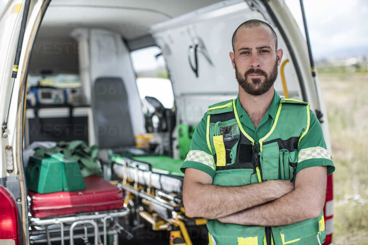 Paramedic standing with arms crossed in front of ambulance - ZEF12175 - zerocreatives/Westend61