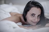 Portrait of smiling young woman lying in bed - ZEF12214