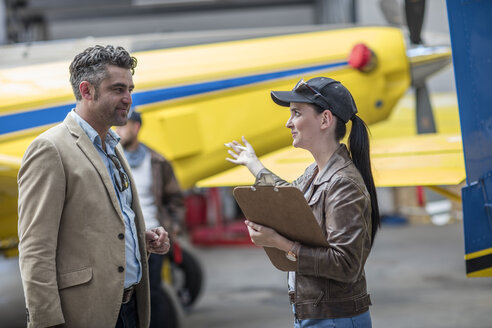 Female pilot talking to business client - ZEF12244