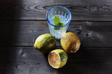 Whole and sliced tiger lemons and glass of infused water - KSWF01780