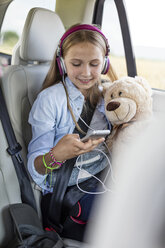 Girl sitting in car, holding teddy bear and listening music - WESTF22341