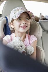 Girl sitting in car, holding teddy bear - WESTF22350