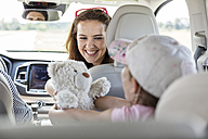 Mother and daughter on road trip sitting in car holding teddy bear - WESTF22353