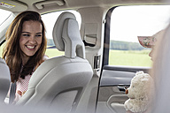Mother and daughter on road trip sitting in car holding teddy bear - WESTF22356