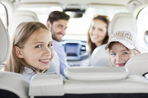 Happy family doing a road trip, looking over shoulder at camera - WESTF22359