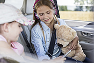 Girls sitting in car with teddy bear - WESTF22362