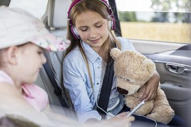 Girls sitting in car with teddy bear - WESTF22362