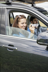 Couple driving in car, woman holding camera - WESTF22365
