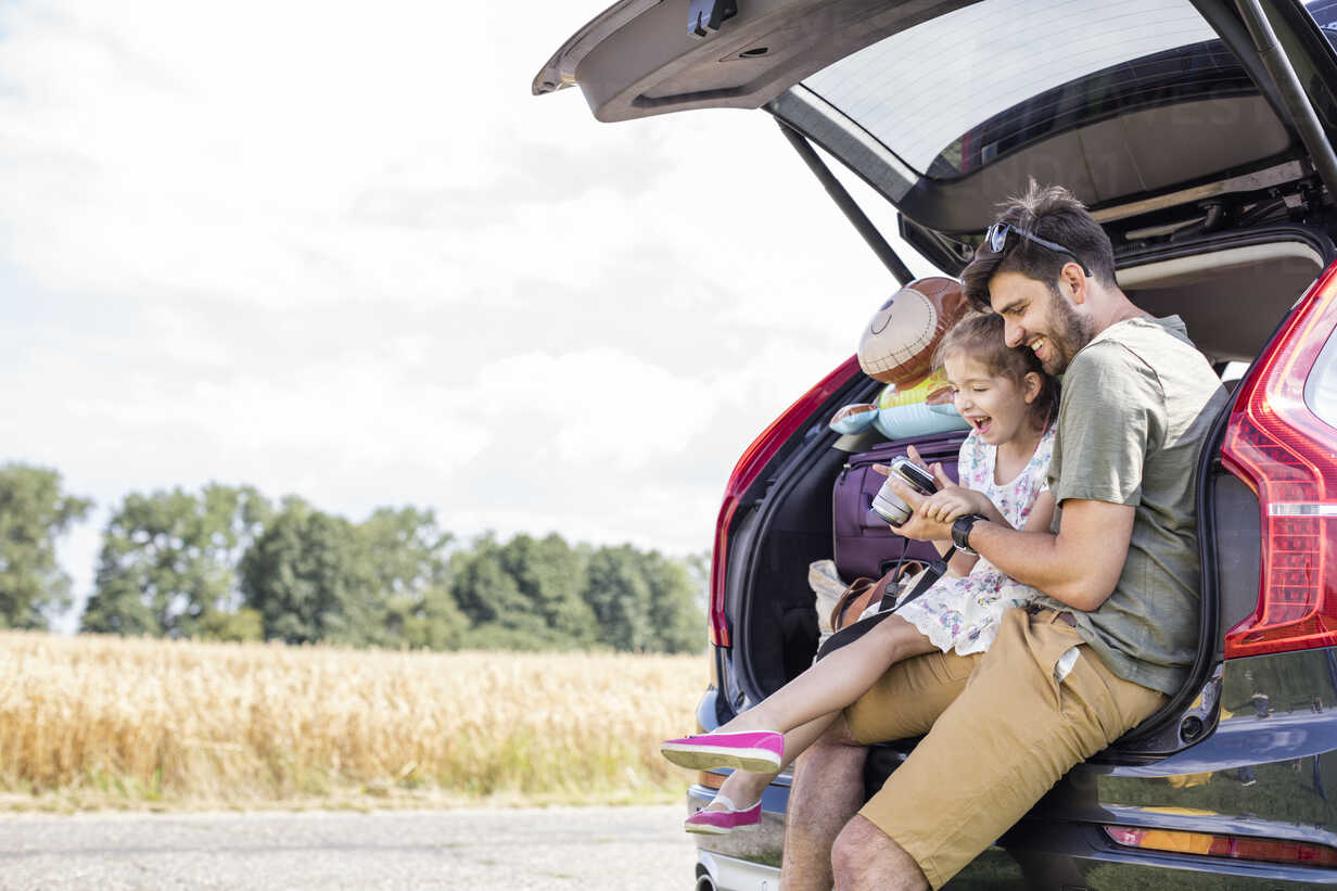 Father and daughter sitting in open car boot looking at camera at break of a road trip - WESTF22377 - Fotoagentur WESTEND61/Westend61