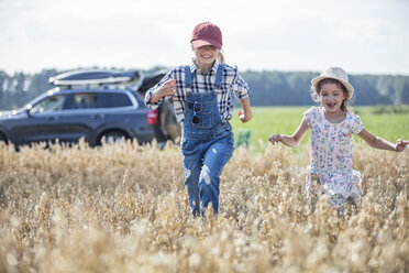 Two laughing girls running in field - WESTF22386