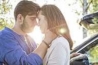 Couple embracing and kissing while on a road trip - WESTF22392
