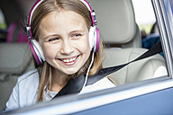 Girl sitting in car, looking out of window, listening music - WESTF22407