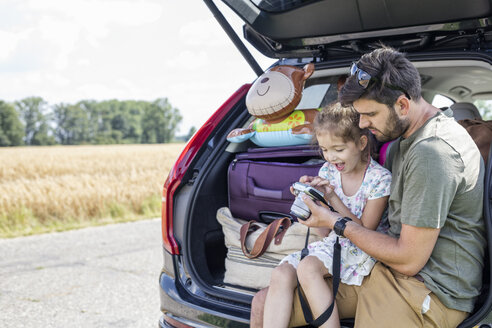 Father and daughter sitting in open car boot looking at camera at break of a road trip - WESTF22416