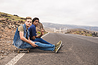 Spain, Tenerife, two friends with skateboard sitting at roadside - SIPF01242