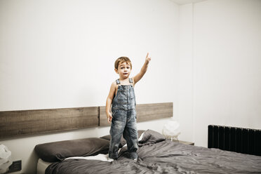 Little boy standing on the bed of his parents pointing on something - JRFF01113