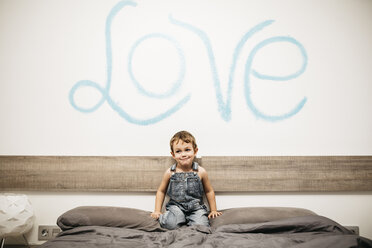 Little boy crouching on the bed of his parents - JRFF01128
