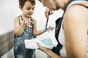 Mother painting little boy's hands blue - JRFF01134