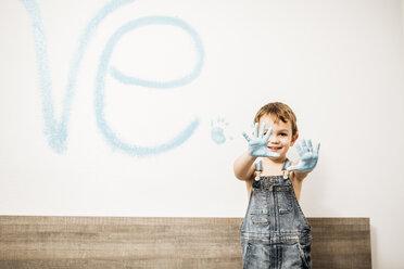 Portrait of smiling little boy showing his palms full of light blue colour - JRFF01137