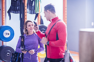 Young man and woman with cell phones and earbuds in gym - ZEF12251