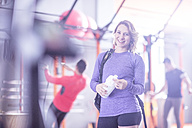 Portrait of smiling young woman in gym - ZEF12254