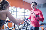 Fitness instrustor talking to woman on exercise machine - ZEF12260