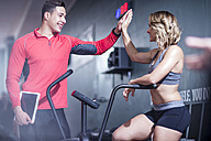 Fitness instrustor high fiving with woman on exercise machine - ZEF12263