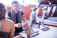 Young man and woman having a refreshment break in gym - ZEF12269