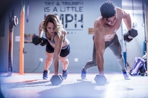 Young man and woman doing dumbbell press ups in gym - ZEF12281