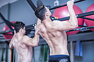 Two young men doing pull-ups in gym - ZEF12290