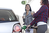 Two women with takeaway coffee fueling car at gas station - ZEF12296