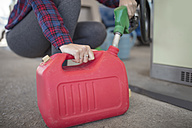Woman filling up canister at fuel station - ZEF12314
