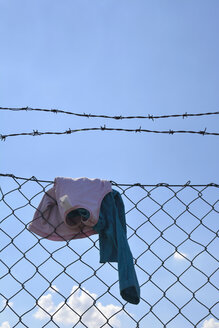 Children clothing hanging on wire mesh fence - AXF00786