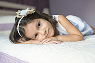 Portrait of little girl lying on bed - JASF01412