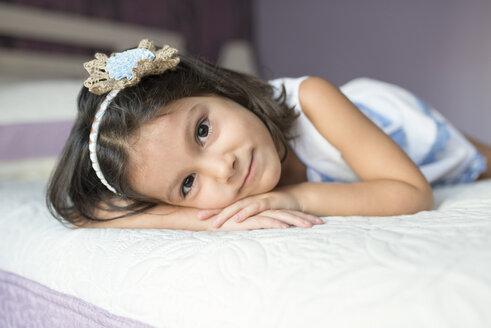 Portrait of little girl lying on bed - JASF01412