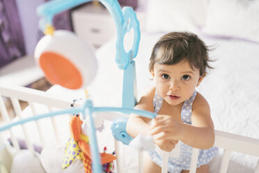 Portrait of baby boy playing on bed - JASF01415